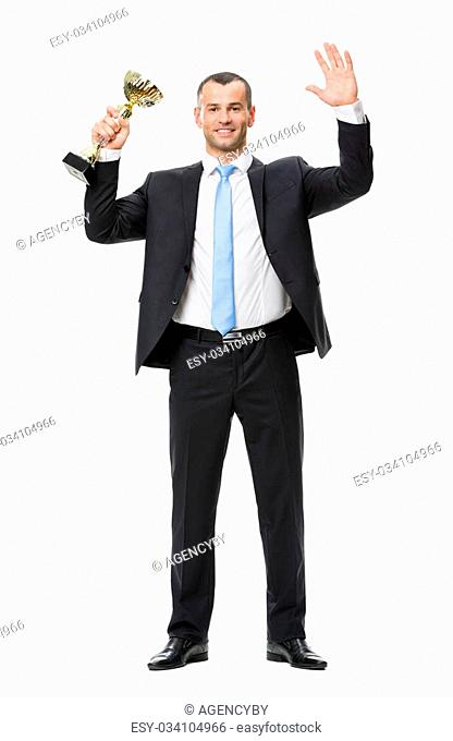 Full-length portrait of businessman with gold cup, isolated on white. Concept of leadership and success