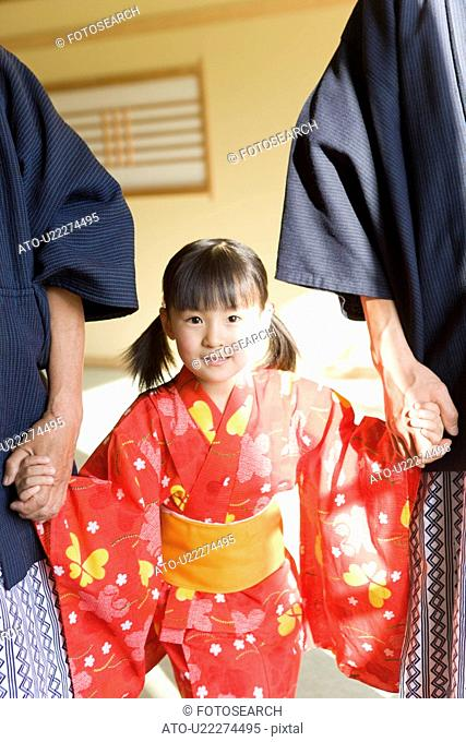 Portrait of a girl with parents standing in Yukata, hand in hand
