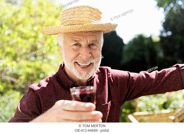 Portrait confident senior man drinking red wine in garden