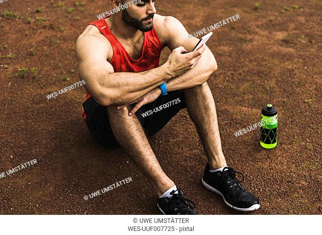 Athlete outdoors sitting on ground looking at cell phone