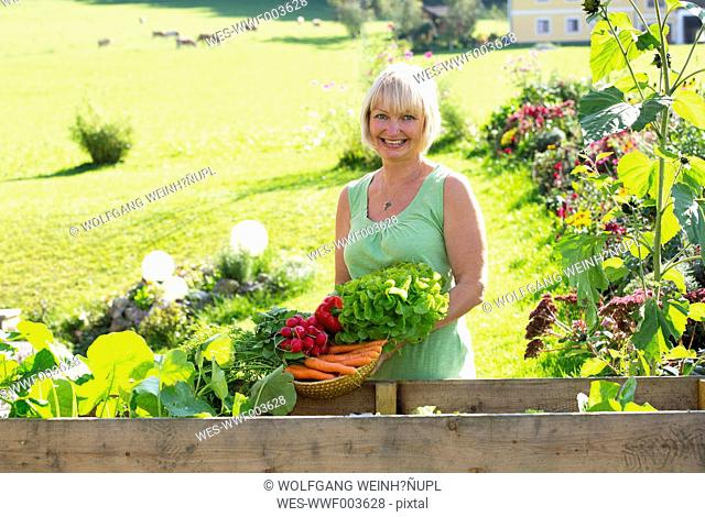 Austria, Mondsee, portrait of happy woman with her vegetable harvest