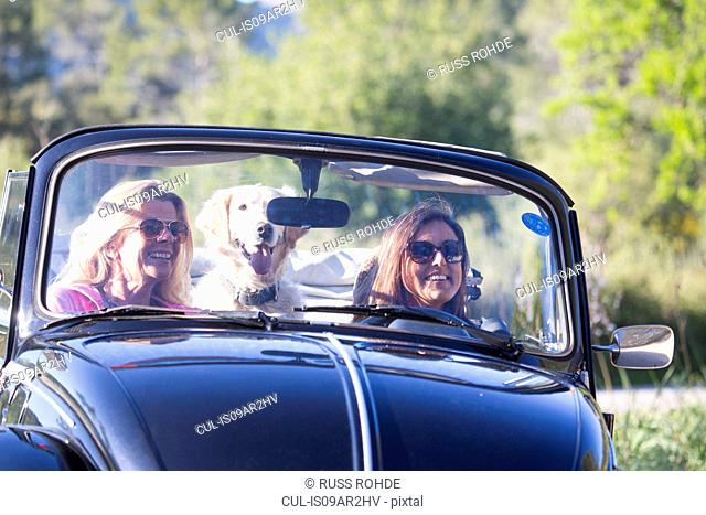 Two mature women, in convertible car, with dog, smiling