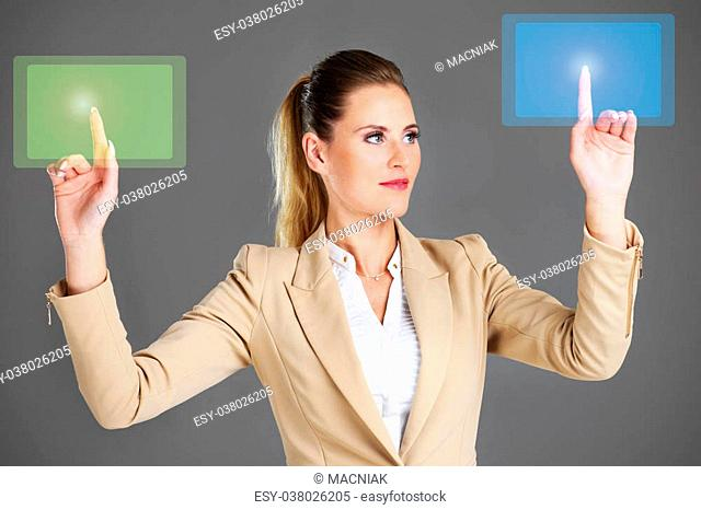 A picture of businesswoman and touchscreen over grey background