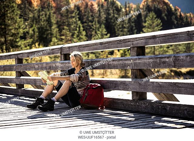 Austria, Alps, woman on a hiking sitting on a bridge reading map