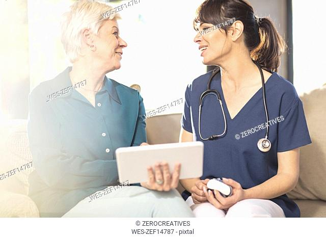Nurse talking to senior woman with tablet at home