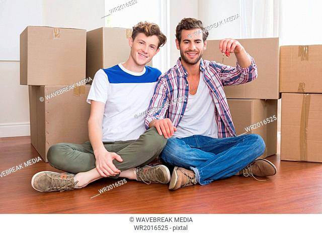 Happy homosexual couple showing new house key