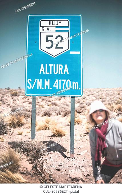 Senior woman standing in front of road sign, Salinas Grandes, Jujuy, Argentina