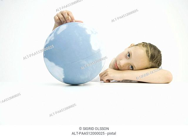 Girl holding globe, head resting on arms, looking at camera