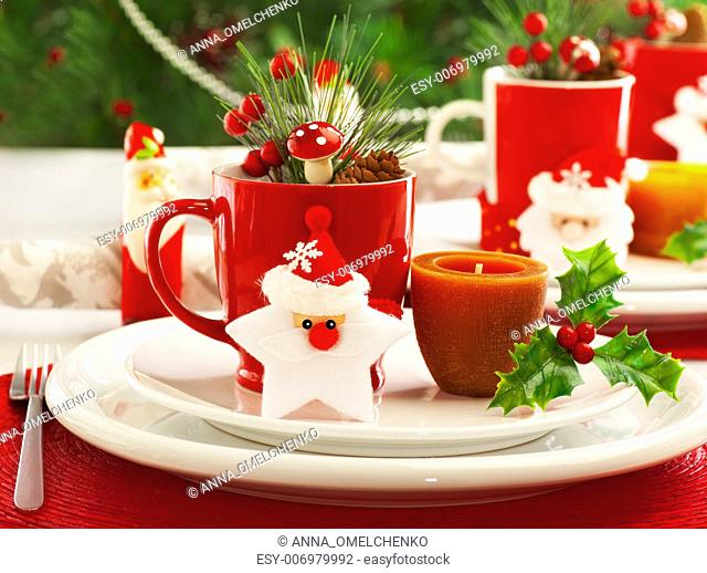 Picture of beautiful Christmas table setting, shining white plate with red cup for coffee decorated holiday dinner, branch of berry and santa claus star on...