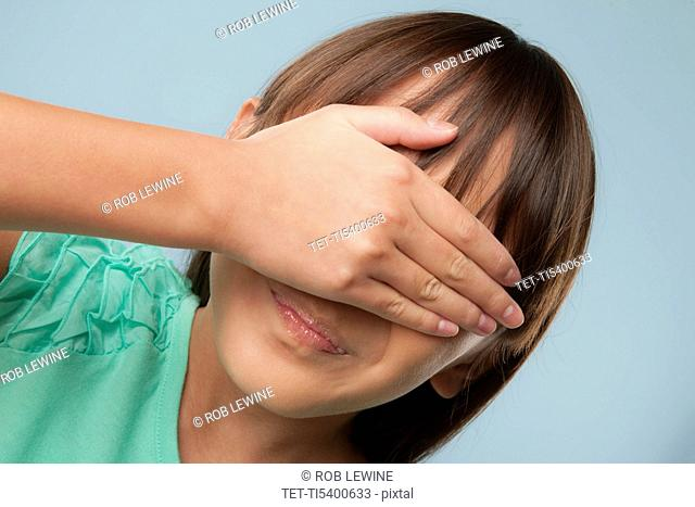 Studio shot of girl 10-11 covering eyes with hand