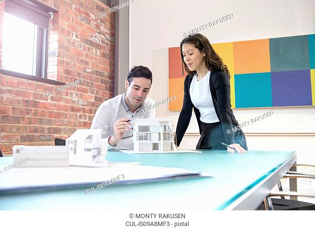 Architects working together on model of building in office