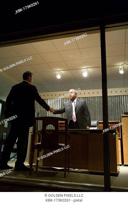 View through window of businessmen in office shaking hands