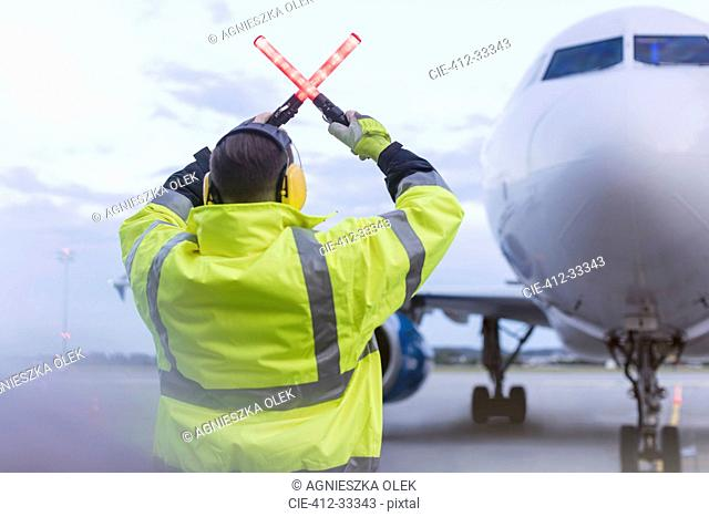 Air traffic controller guiding airplane with wand lights on tarmac