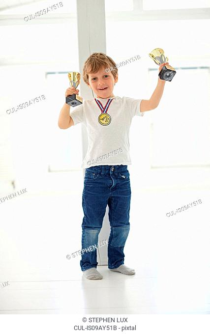 Portrait of boy holding up trophies and wearing gold medal