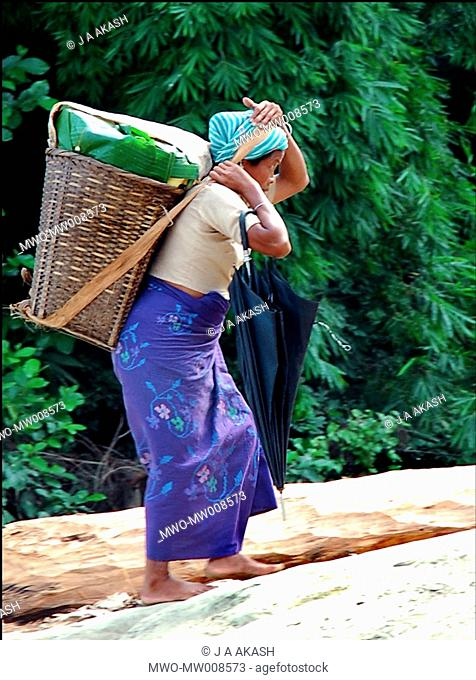 A Moorong tribal woman carrying goods on her back to the market at Bandarbans, Bangladesh July 29, 2006