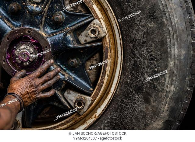 A Colombian car mechanic applies a lubricant grease on a truck axle cap during the maintenance service in Barrio Triste, Medellín, Colombia, 18 April 2018