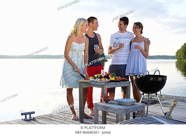Four people on jetty cooking meal