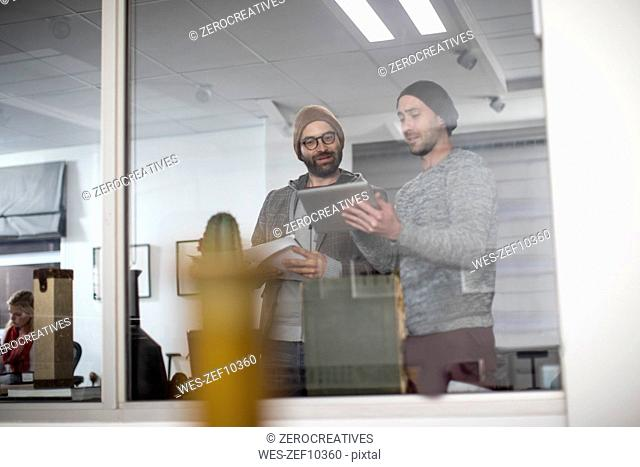 Two creative professionals discussing ideas on digital tablet
