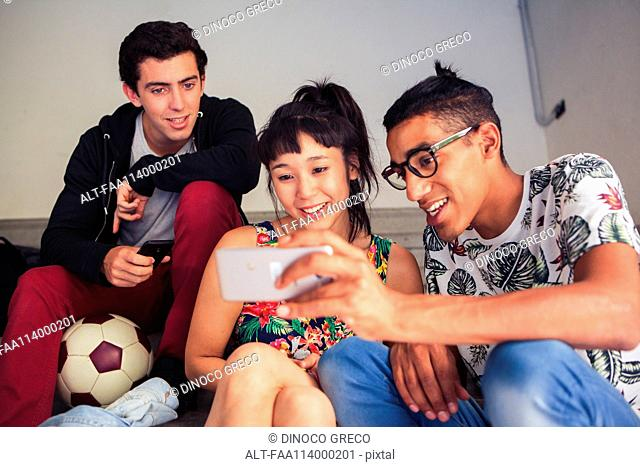 School friends looking at smartphone together
