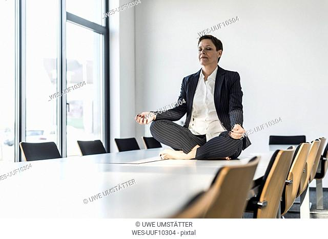 Businesswoman sitting on conference table meditating