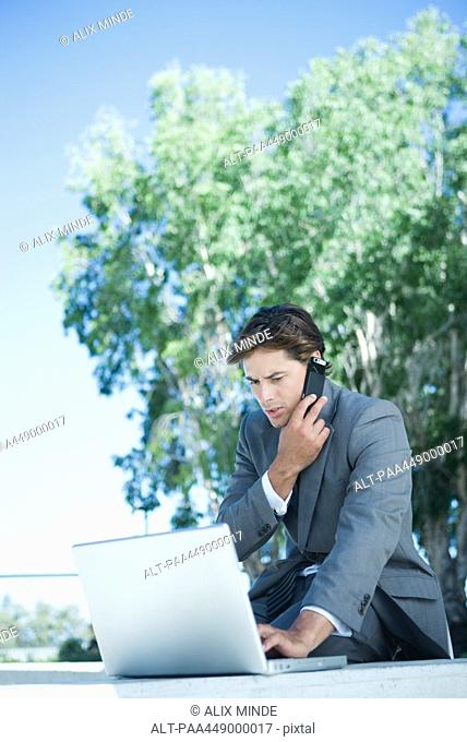 Businessman using laptop and cell phone, outdoors