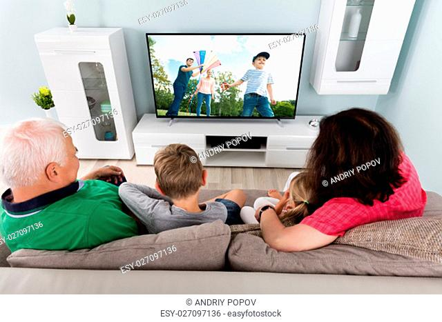 Family With Kids Watching Movie On TV Together At Home
