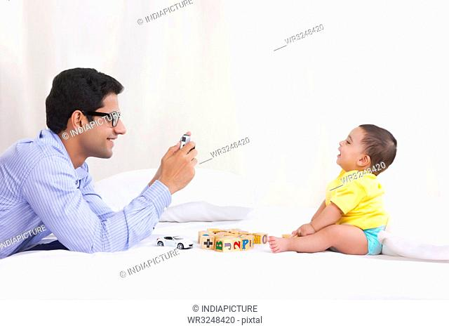 Father taking picture of baby playing
