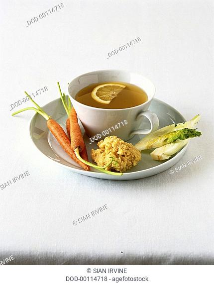 Cup of clear soup garnished with lemon slice, served on white ceramic plate with hummus and raw carrots and sliced fennel
