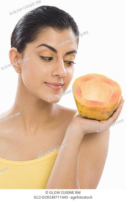 Close-up of a woman holding a half of papaya