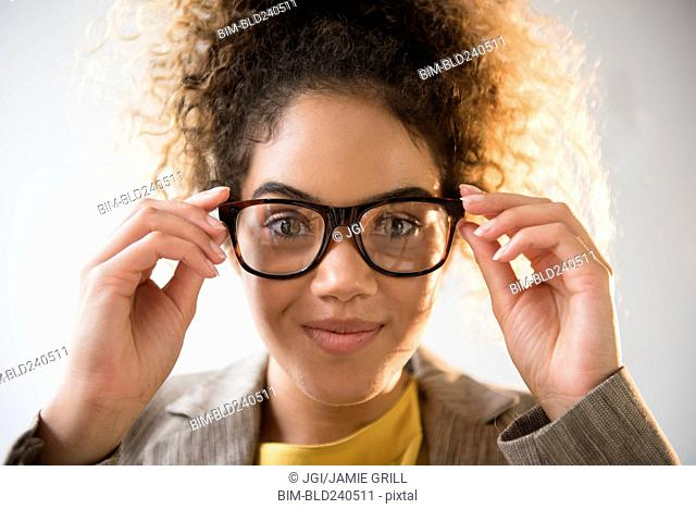 Mixed Race woman adjusting eyeglasses