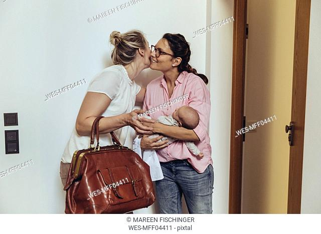 Woman greeting midwife at her homeƒ.s apartment door