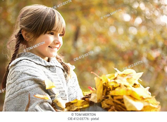 Smiling girl playing in autumn leaves
