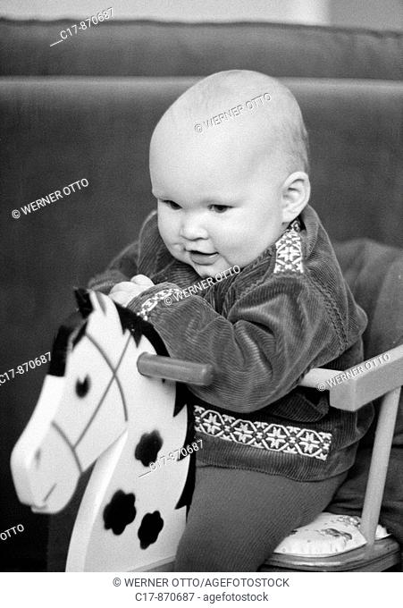 Seventies, black and white photo, people, children, baby sits on a rockinghorse, laughing, aged 6 to 12 months, aged 1 year, Christina