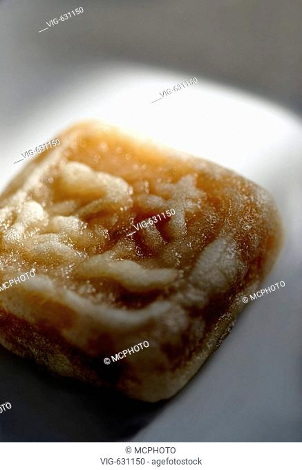 This macro stock photo shows a typical cubical shaped Japanese Sweet on a white plate. On top have Japanese kanji signs been formed into the sweet