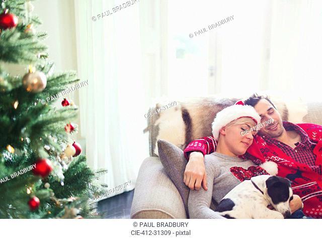 Serene couple cuddling with dog on sofa next to Christmas tree