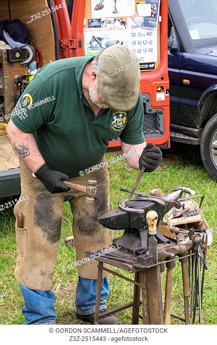 A farrier preparing a horseshoe for fitting at the Essex Country Show, Barleylands, Essex
