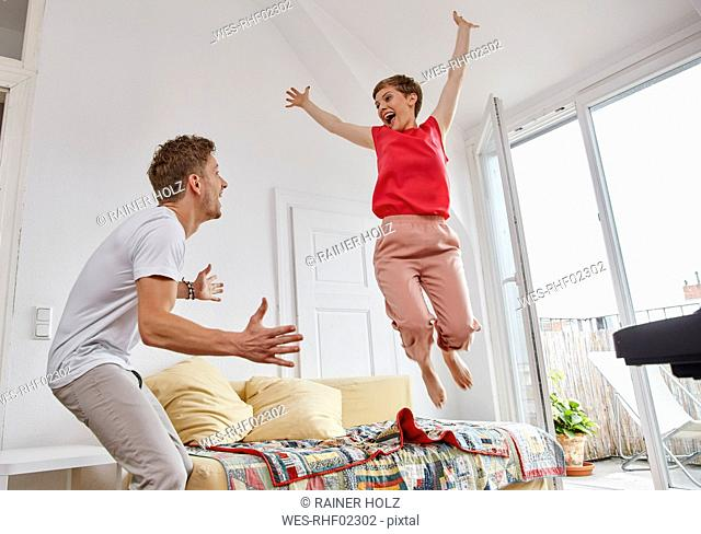 Excited couple in living room at home