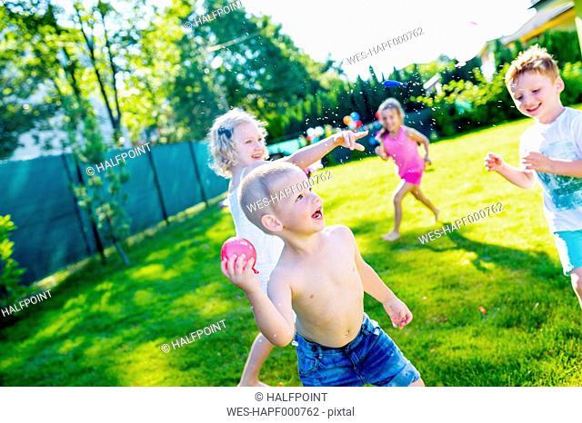 Children having fun with water bombs in the garden