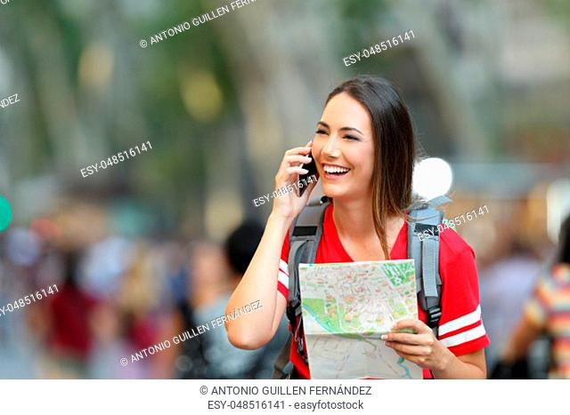 Teenage tourist talking on phone and holding a map in the street