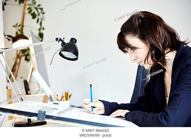 A woman working on a graphic on a drawing board, outlining letters with a pencil