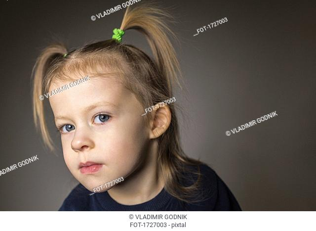 Close-up portrait of cute girl with pigtails against gray background