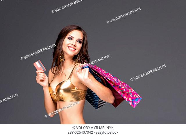 Young woman in a gold swimsuit with shopping bags and credit card on a gray background
