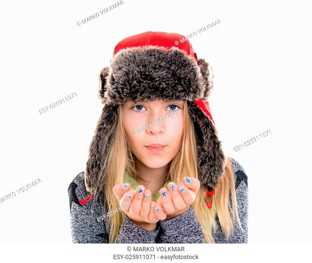 nice blond girl with fur cap and scarf blowing in to the camera