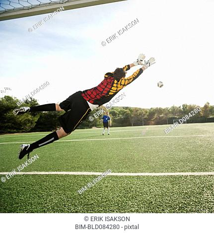 Mixed race goalkeeper in mid-air protecting goal