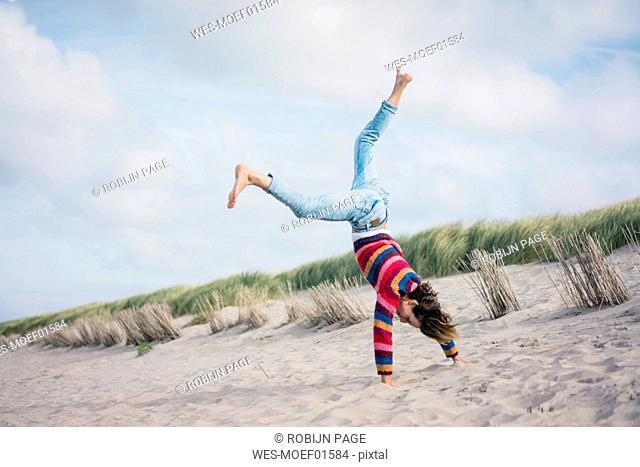 Mature woman having fun, cartwheeling on the beach