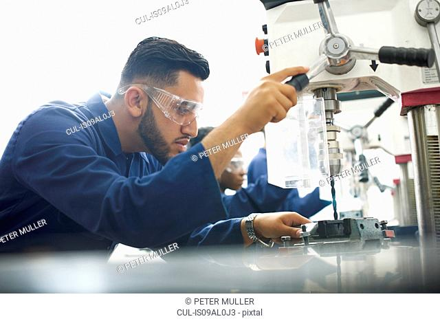 Male student using drilling machine in college workshop