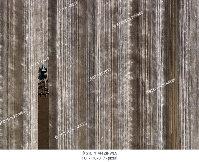 Aerial view agricultural tractor plowing field, Bakersfield, California, USA