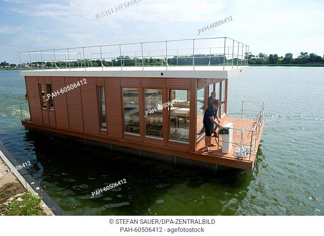 Staff members of 'Hausboot Werft Peenestrom GmbH', manufacturer for tourist house boats, travel on a house boat on the Peenestrom near Wolgast, Germany