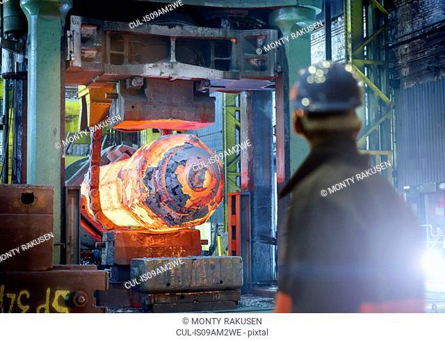 Steelworker inspects hot steel in forging press in steelworks