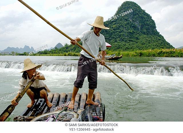 Chinese couple transporting tourists along the Yulong River on a bamboo raft, Yangshuo, Guangxi, China
